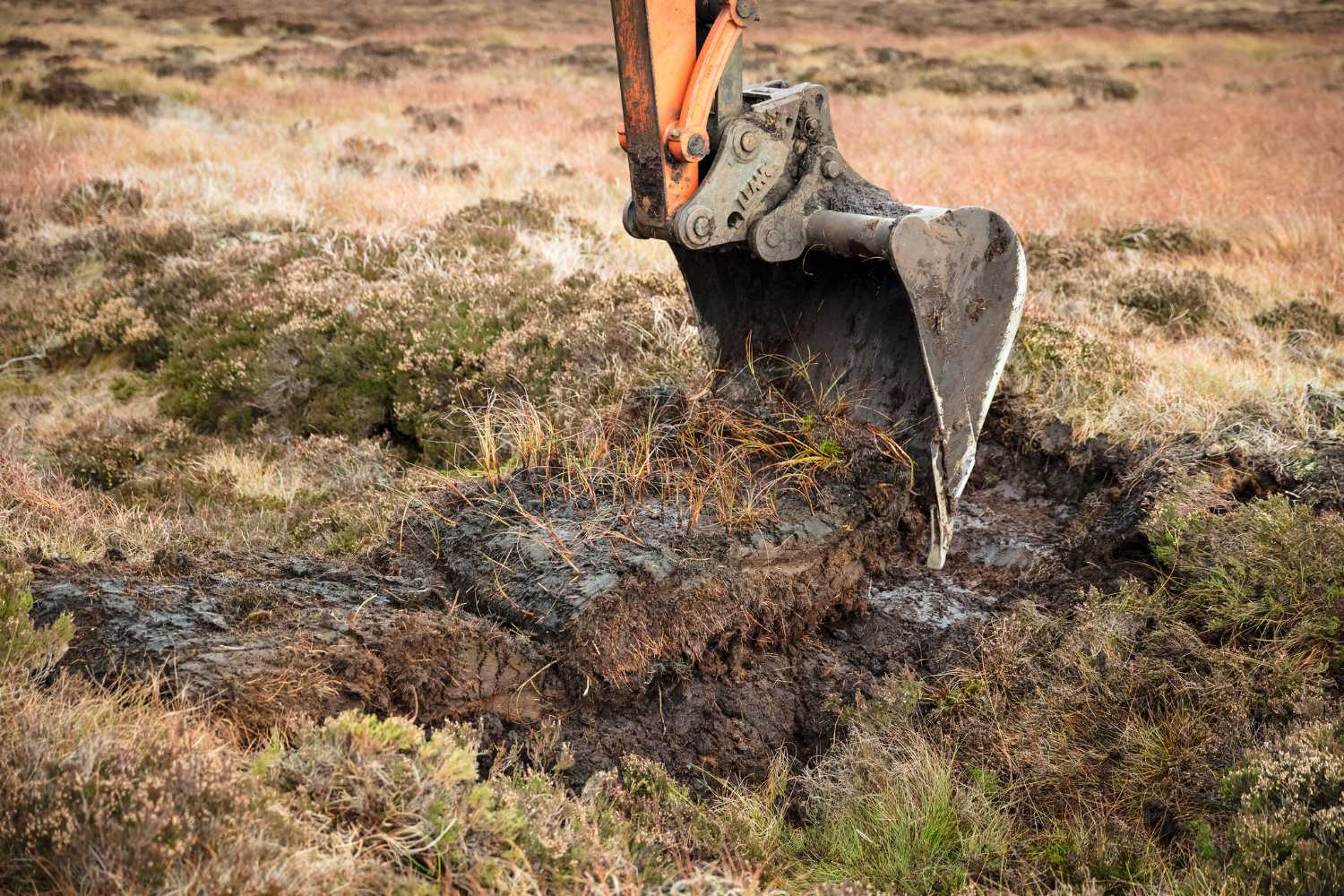 A peat dam being created with a digger