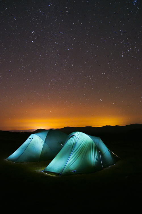 Image of two tents lit up in front of a clear night sky